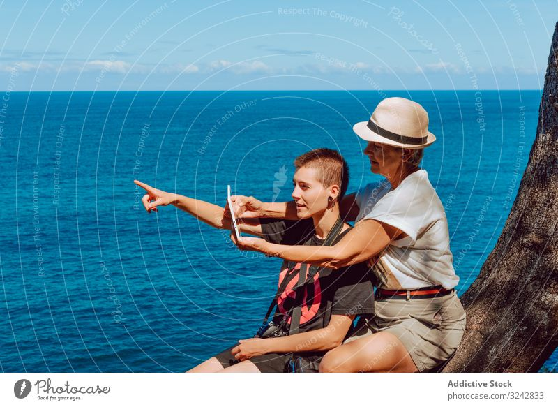 Stylish woman with tablet in hands and elderly lady women mature sea rocky finger pointing using water blue sky vacation summer ocean happy tropical beach