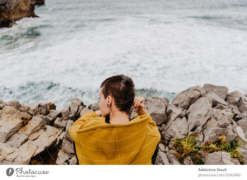 Woman in yellow hoodie on stony shore woman solitude travel wave stone watching dream harmony contemplation lonely thoughtful sea ocean horizon freedom