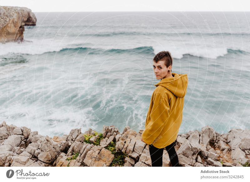 Person in yellow hoodie on stony shore solitude travel wave stone watching dream harmony standing contemplation lonely thoughtful sea ocean horizon freedom