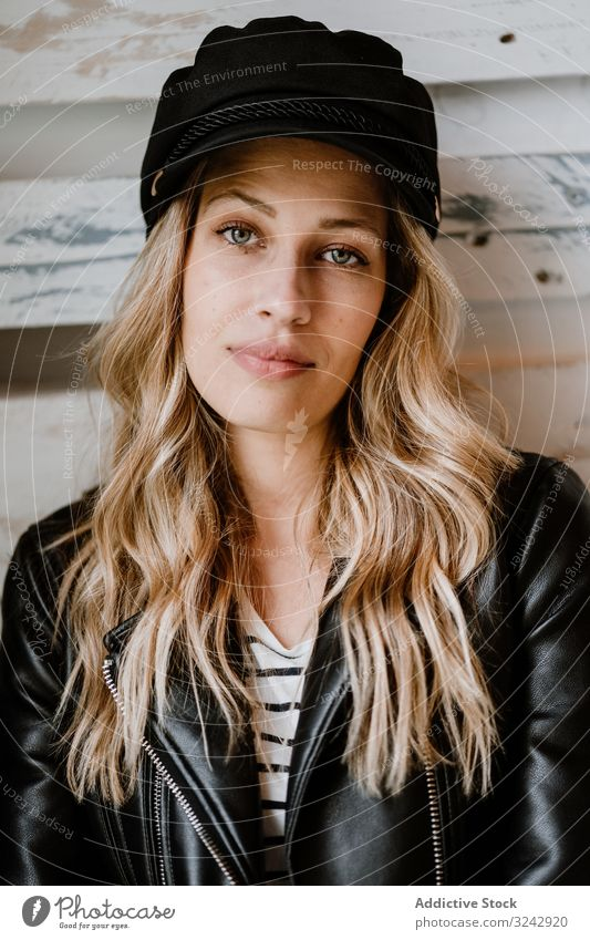 Beautiful blonde woman stylish pensive natural trendy contemplate curly female long haired beauty leather jacket attractive alone casual cap hat romantic