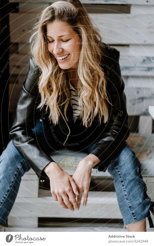 Woman sitting in a wooden bench in cafe woman stylish blonde waiting design trendy creative clothing leather jacket casual denim bright curly model female vogue