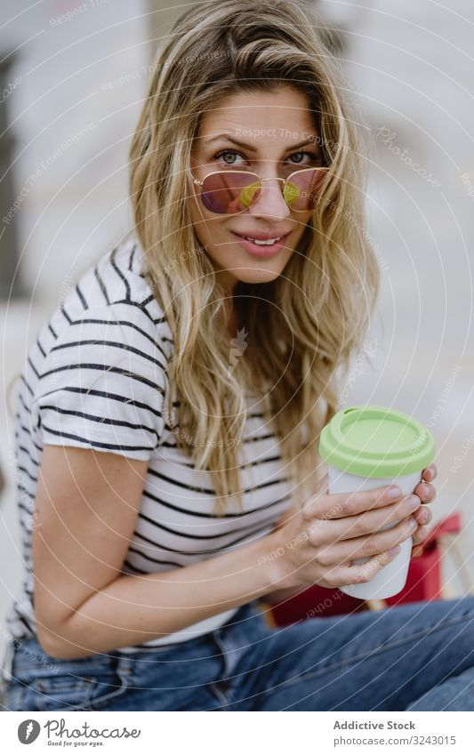 Happy woman with disposable cup of coffee sitting on street bench city seafront happy joyful enjoy casual rest young female laugh smile excited beautiful drink