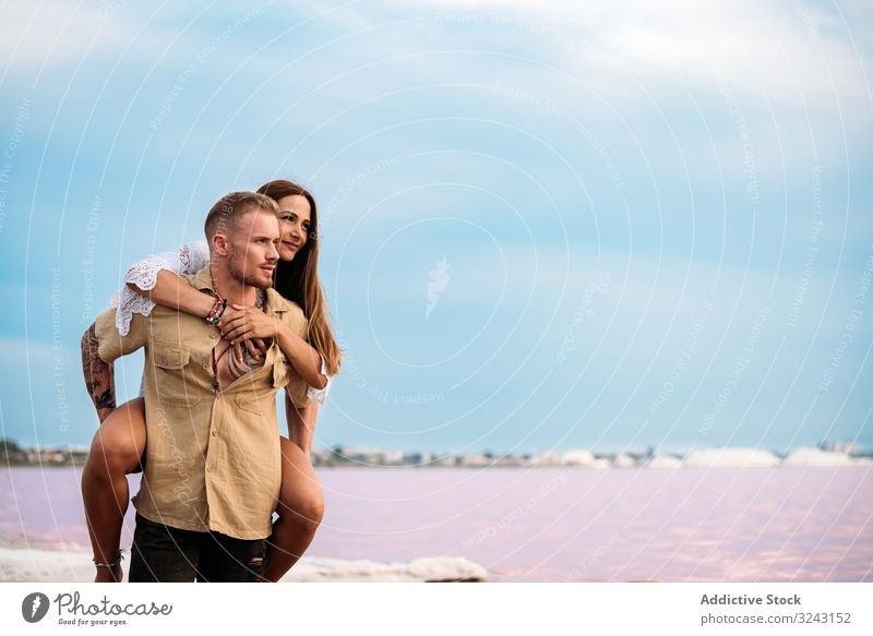 adorable couple giving a piggyback ride on an amazing beach of pink water blue sky lifestyle Torrevieja holding hands sunny love relationship brine paradise