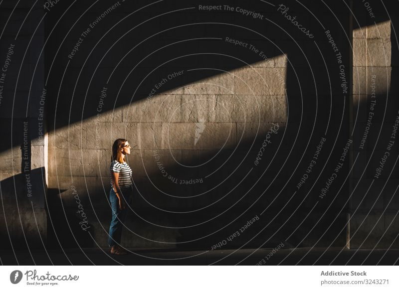 Woman standing in sunlight in dark passage woman shadow wall city street casual spot female rest relax summer town building exterior structure construction