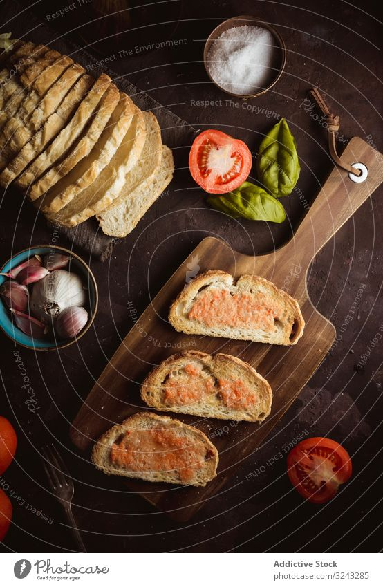 Spices and vegetables near toasts sauce ingredient spice tomato salt garlic basil oil bread cutting board food snack delicious tasty bruschetta yummy delectable