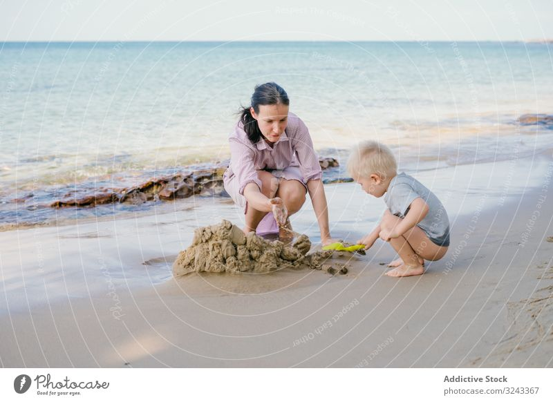 Toddler and mother playing with sand on beach against blurred seascape in sunny day kid child tropical game rest vacation son preschool parent pleasure idyllic