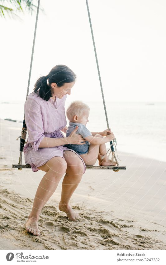 Joyful kid swinging with mother against blurred seascape child beach relax together tropical play pensive son nature preschool fresh parent support pleasure