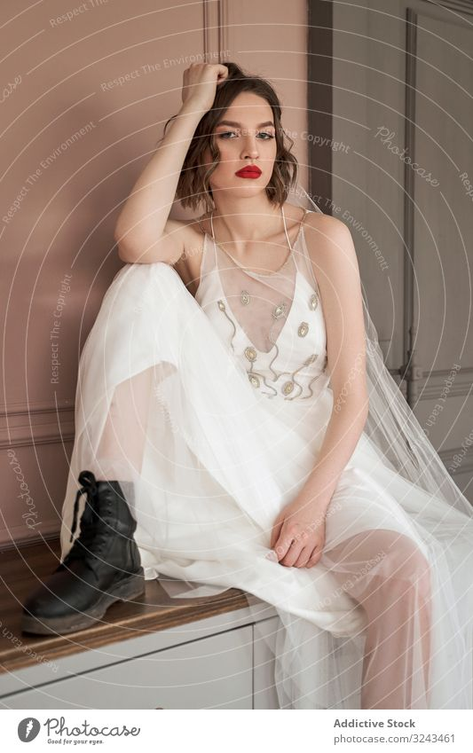 Attractive adult confident lady in white dress and military black shoes looking at camera woman wedding dress red lips provocative elegant cool rude beauty