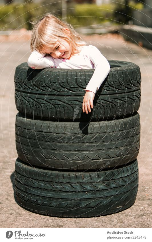 Little girl resting in stack of tires kid naughty fun play prank tyre little happy joy child childhood active cheerful leisure smile laugh game hide hole joke