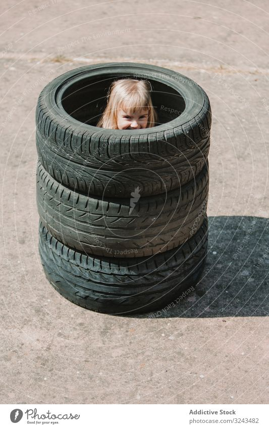 Little girl hiding inside stack of tires kid naughty fun play prank tyre little happy joy child childhood active cheerful leisure smile laugh game hide hole