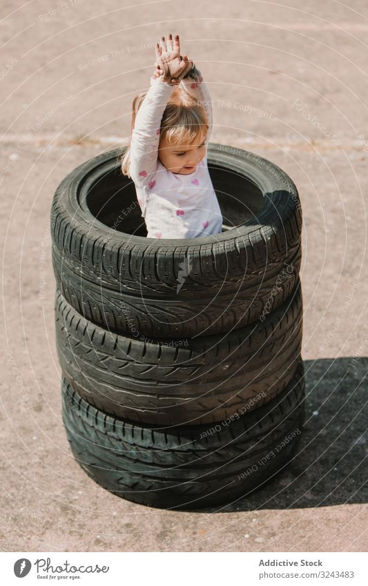 Little girl standing in stack of tires kid naughty fun play prank tyre little happy joy child childhood active cheerful leisure smile laugh game hide hole joke