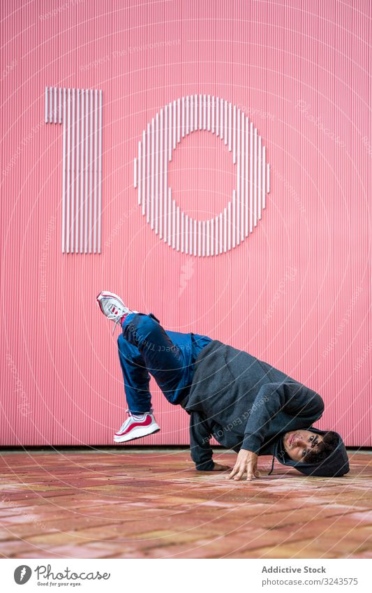 Young male teenager breakdancing on street cool sport dance hip hop style movement fashion young urban fun contemporary music motion action culture freestyle