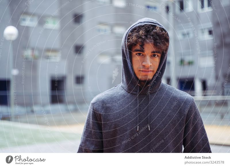 Wistful man in casual clothing in yard hoodie street city cold young ethnic hood up lifestyle hipster stylish thoughtful fashionable youth guy season male curly