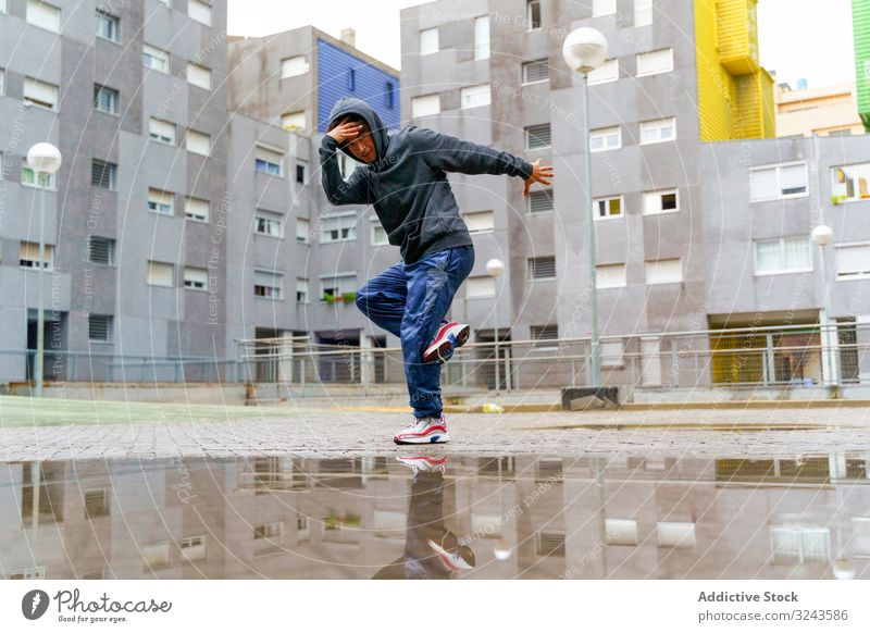 Hipster in casual wear break dancing on street man urban culture funky sport dance hip hop style movement fashion young music yard rainy motion action plash