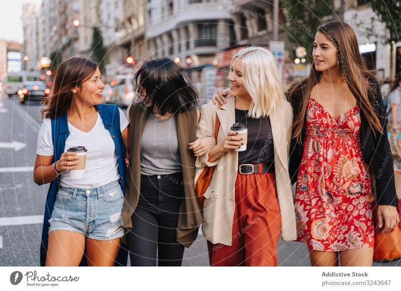 Female friends walking on street and chatting happily stroll drink smile embrace hug women together meeting to go stylish young casual trendy beverage coffee