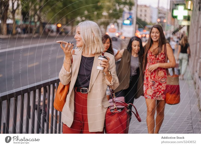 Cheerful woman recording audio message walking on street smartphone smile using drink takeaway stylish city send casual female young mobile app cheerful happy