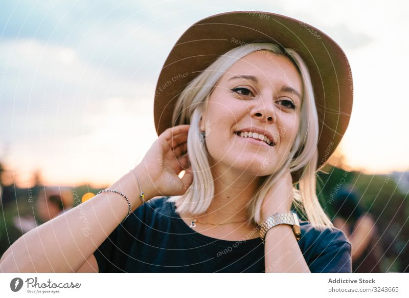 Dreamy blond woman resting in park smile dream touching hair inspiration elegant stylish happy dreamy female headgear young cheerful relax lifestyle summer joy