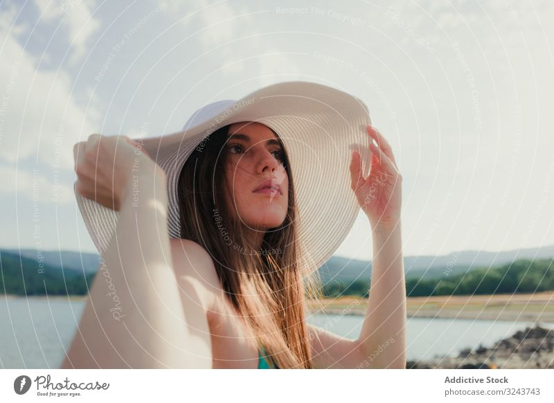 Young woman in hat resting on beach lake summer young dreamy cloudy sky female water vacation weekend lifestyle nature countryside headgear weather lady calm