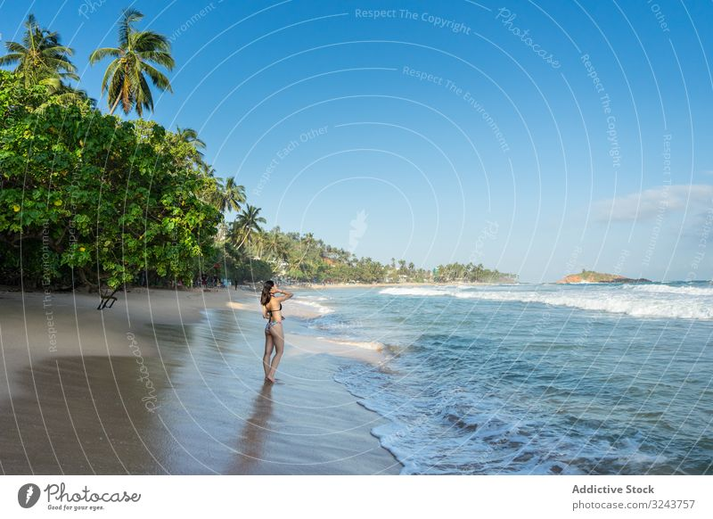 Young lady in water on sand beach with tropical forest Mirissa beach Sri Lanka island woman shore splashing cheerful young green attractive female nature fresh