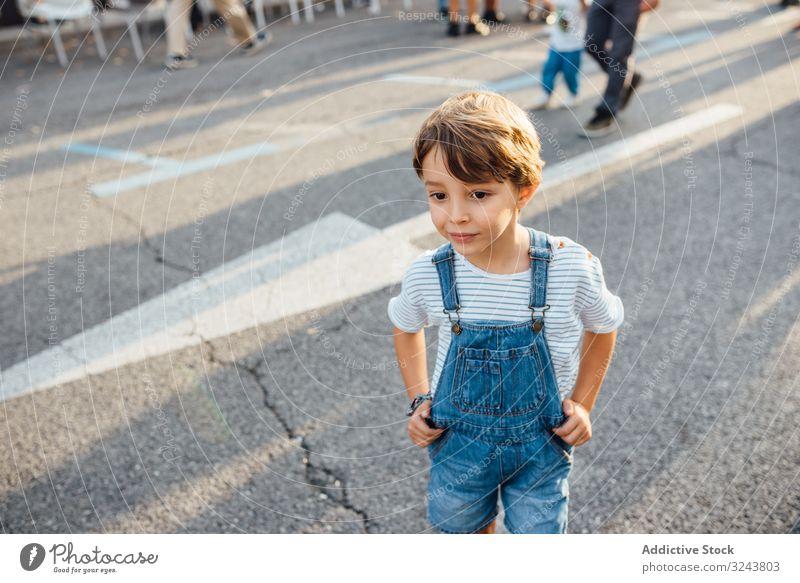 Little boy looking away on street city curious casual little adorable modern rest hands on waist road asphalt urban kid child lifestyle relax wait denim outfit