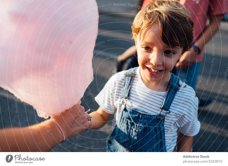 Cheerful boy taking candyfloss from vendor funfair excited smile street city sweet seller kid child joy happy urban town cotton candy casual delighted