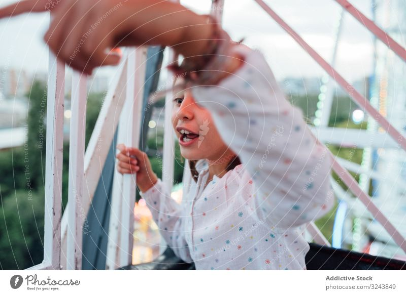 Cheerful girl riding Ferris wheel with parent ferris wheel ride excited mother fun autumn amusement park laugh kid child daughter entertainment observation
