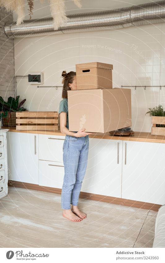 Young woman carrying big carton boxes in house container property moving female relocate home household package apartment delivery unpacking heavy parcel casual