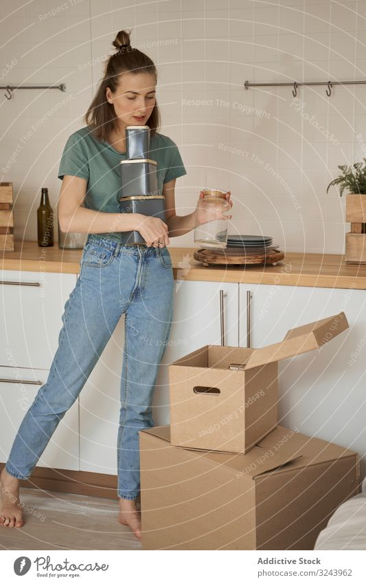 Careful woman holding containers with hand and taking cans out of box apartment unpack kitchen moving female cardboard carton home delivery receive opening