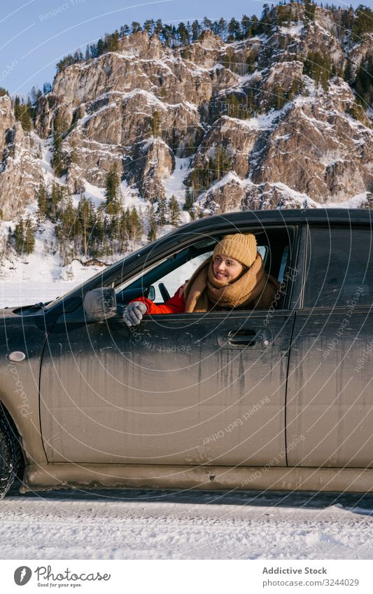 Woman leaning out car window on snowy valley woman mountain winter siberia road trip happy enjoy smile nature scenery rock hill cold landscape scenic russia