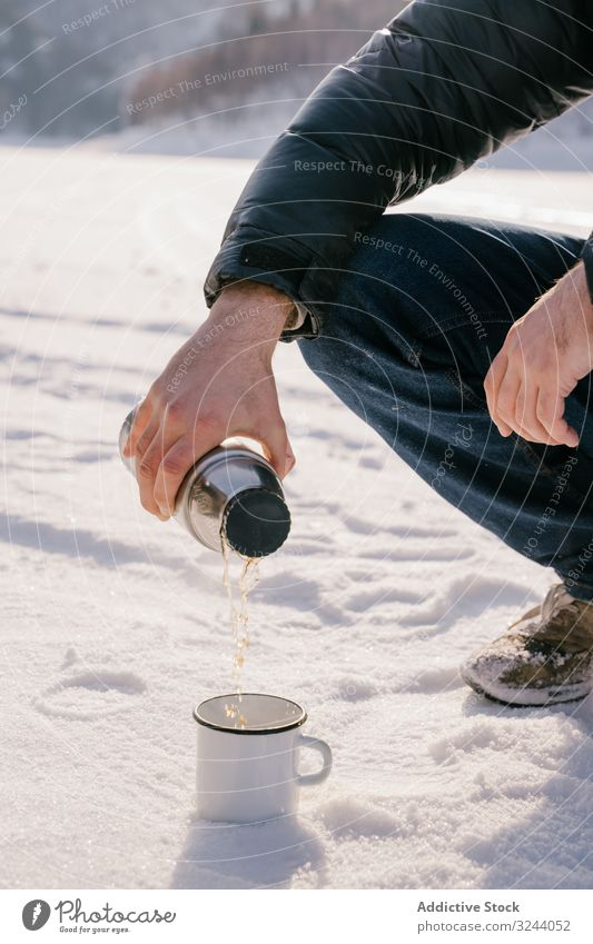 Man pouring tea from thermos bottle on winter day man snow siberia nature cold warm up russia male sit hot break rest recreation drink relax adventure activity