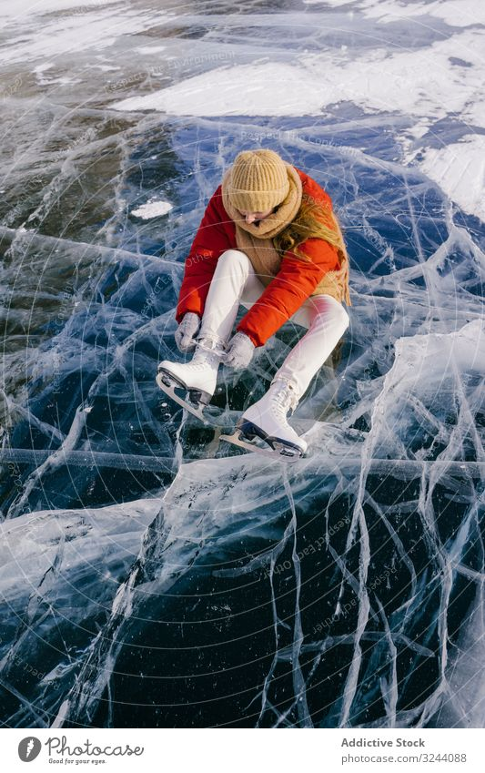 Woman sitting on frozen river and tying the shoelaces woman snow boots skates putting on winter change siberia cold sportswear russia female white adventure