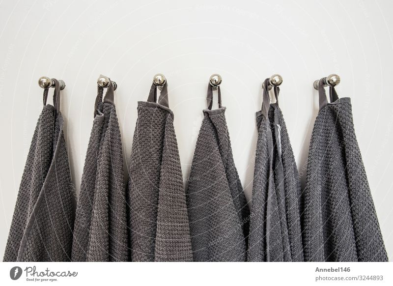 Grey towels hanging in a row, prepared on hanger. white wall Spa Vacation & Travel House (Residential Structure) Bathroom Cloth Metal Steel Clean Soft Gray