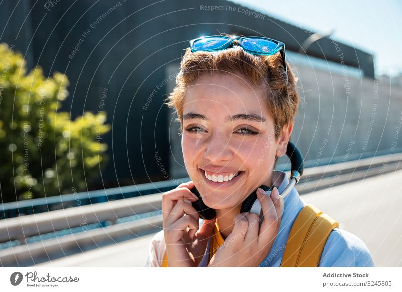 Playful trendy woman on street in sunshine covering camera with hands bright smile playful sunglasses millennial headphones happy charm human face vivid
