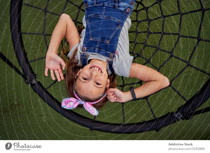 Happy girl having fun on basket swing happy play carefree teenager jumpsuit spider web lying smile playground enjoy excited playful lively child cheerful