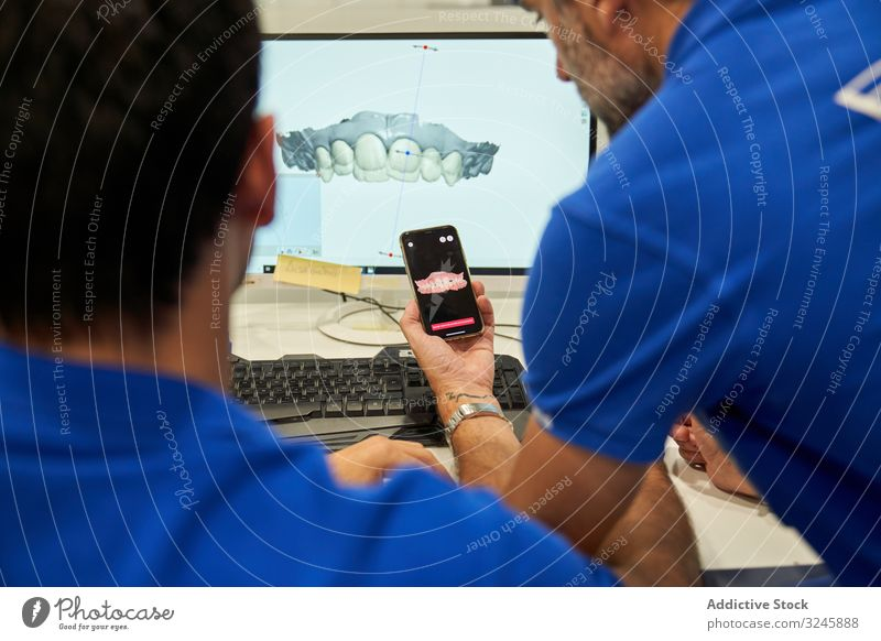 Anonymous orthodontists comparing dental models in lab 3d computer examine monitor smartphone compare laboratory men teeth hi tech engineering doctor clinic