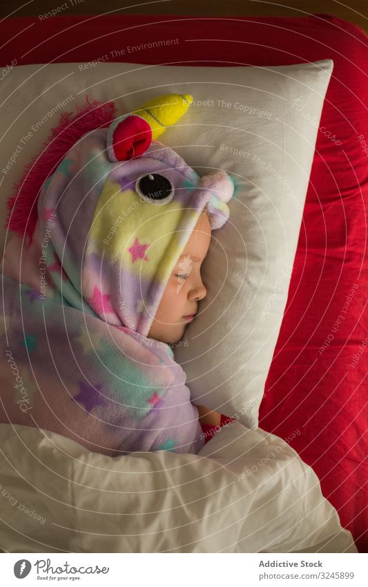 Girl in unicorn pajama sleeping in bed kid child kigurumi girl blanket red white dream lying cute little childhood night bedtime home relax pillow rest adorable