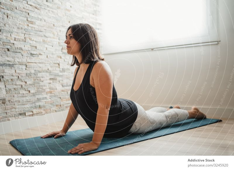 Woman meditating at home woman meditation yoga pose mat practicing morning room relaxation young brunette female wellness fit healthy calm zen peaceful activity