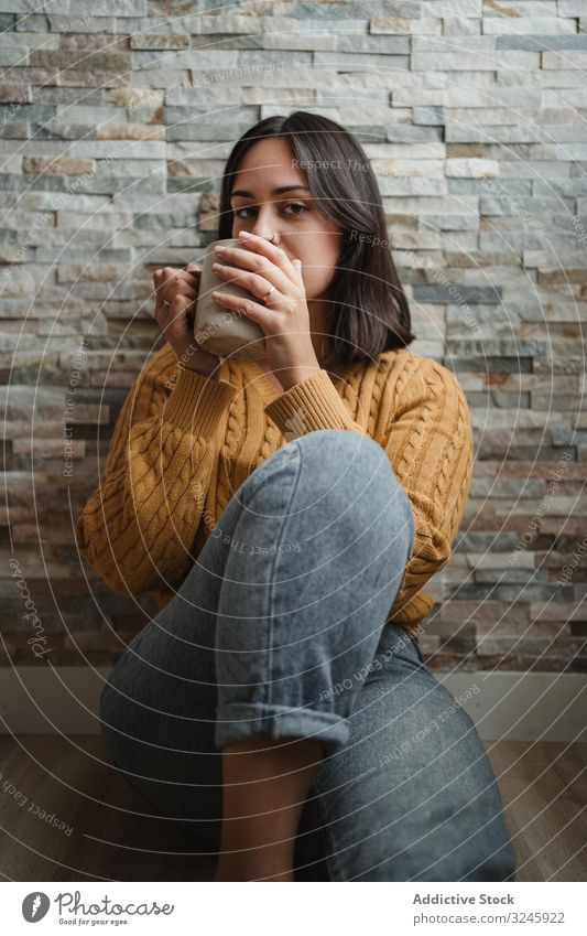 Woman drinking hot tea at home woman mug sweater coffee sit floor jeans female cup beverage young hold relax enjoy recreation warm up cold pullover room house