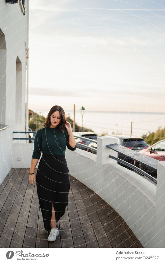 Pensive woman walking on balcony house coast riverside seaside thoughtful pensive casual young calm home wooden handrail building rest relax female brunette