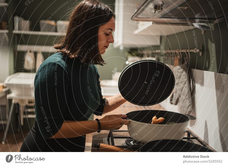Woman opening lid of pan in kitchen woman stove cooking pot house preparing home checking young female brunette casual hold stand household homey food homemade