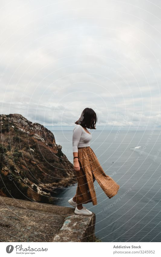 Lonely woman standing on cliff against seascape with cloudy sky coast height freedom water balance viewpoint highland danger fresh female solitude decision