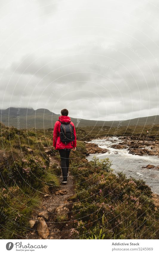 Tourist hiking along stream in meadow against mountain in clouds tourism trail water river adventure footpath trip travel environment person range wilderness
