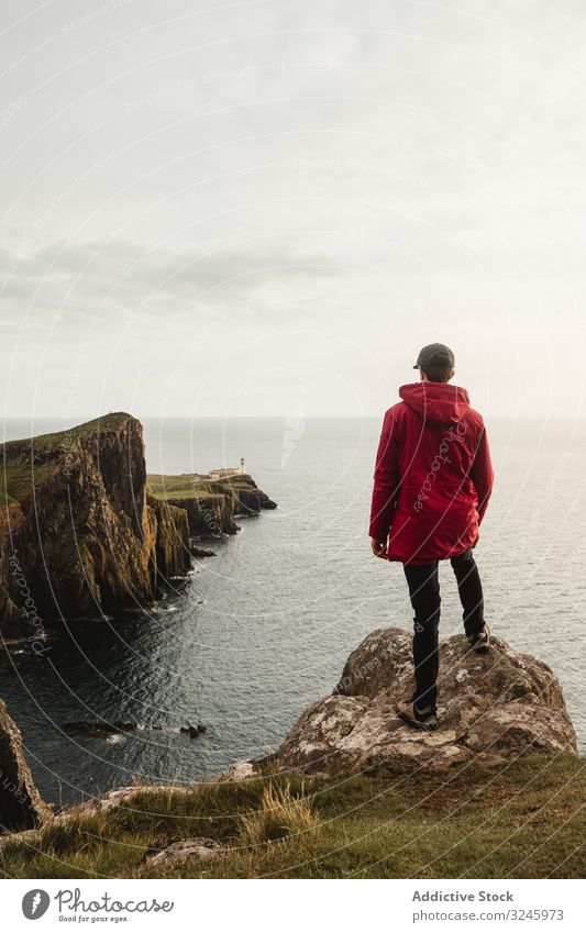 Lonely tourist standing on rocky coast against tranquil sea water under gray sky cliff adventure height viewpoint highland trip fresh wanderlust freedom woman