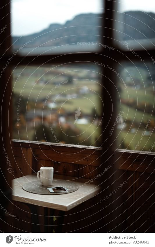 Small table with cup of coffee and photos on terrace on cloudy morning nature mountain tea beverage memory rural modern apartment balcony house wooden interior
