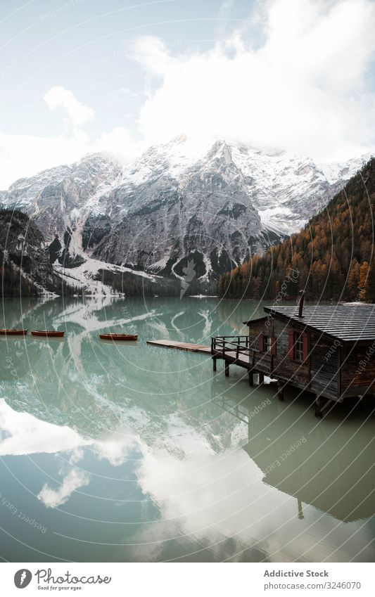 House on stilts on lake near mountains house boat wooden reflection nature travel water landscape sky scenery view tourism vacation clouds holiday adventure