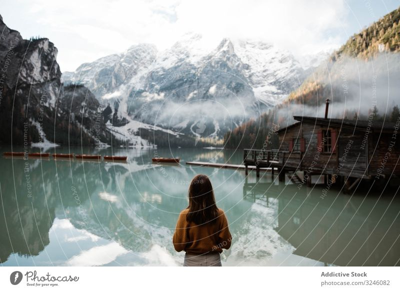 Resting woman in casual wear delighting in views near lake and mountains tourism house water boat fog cloudy mist travel landscape vacation adventure nature