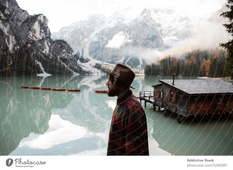 Resting man in casual wear delighting in views near lake and mountains tourism house water boat fog cloudy mist travel landscape vacation adventure nature