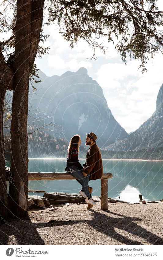 Male and female travelers sitting on fence near lake and mountains couple nature shore pine tree big sunlight holding hands wooden summer adventure lifestyle