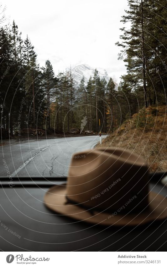 Hat inside a car at lonely highway amid mountains route sky cloud travel tourism landscape road asphalt journey tree season beautiful scenic freedom forest