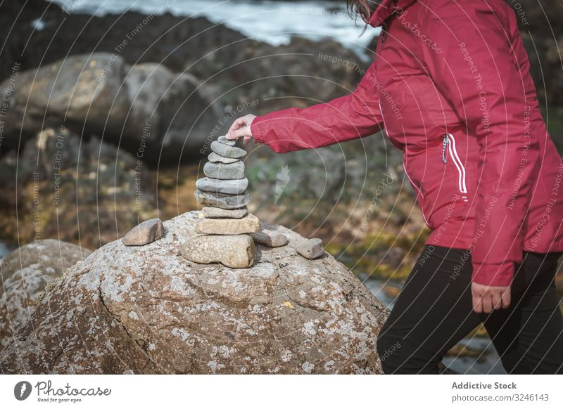 Tourist balancing stones during travel in rocks tourist balance pyramid woman building equilibrium cairn landscape cliff scenic connection nature old ancient